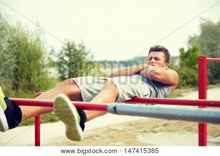 fitness, sport, exercising, training and lifestyle concept - young man doing sit up on parallel bars in summer park