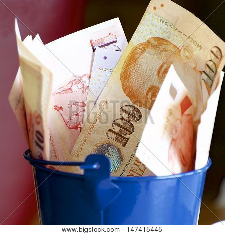 A blue bucket full of Singaporean notes.