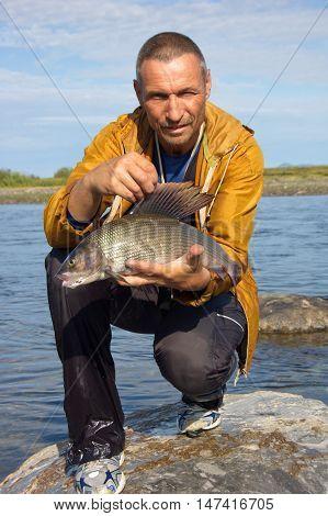 Fisherman caught a trophy grayling. Fishing on Polar Ural Mountains.