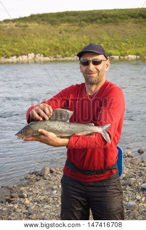 Fisherman caught a large grayling. Fishing on Polar Ural Mountains.