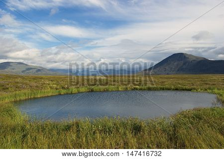 Small lake in the mountain tundra. Journey through the Polar Urals.