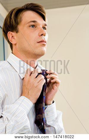 Portrait of serious businessman tying his necktie