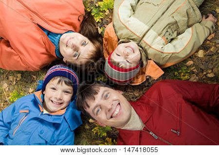 View from above of four smiling people lying on the land