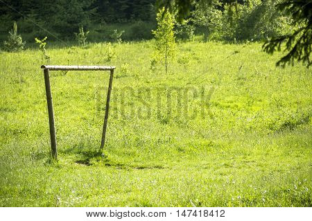 the primitive handmade wooden footbal goal at the meadow