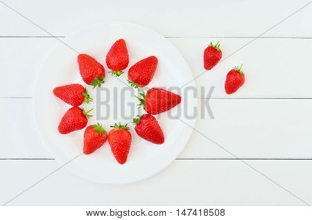 Strawberries on a white table. Strawberries on a white plate. Beautifully decomposed strawberries