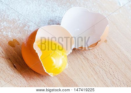 Cooking or baking background with close up broken egg, yolk in eggshell, flour on a wooden background