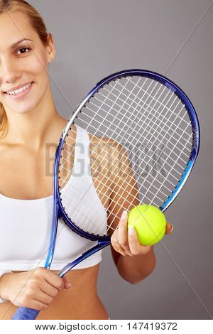 Partial portrait of young girl with tennis racket