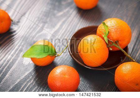 Several ripe mandarines on a dark wooden table