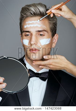 Beautician applying cream by brush on man's face. Beauty eye contour wrinkle cream or anti-aging skin care cream. Beauty & Skin care concept.