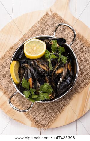 fresh cooked mussels with lemon slices and parsley in a metal bowl