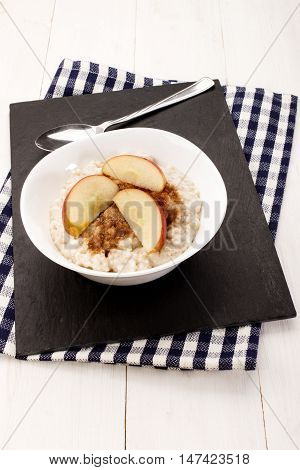 with milk boiled porridge apple pieces cinnamon and sugar in a white bowl