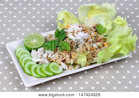 Fried rice with crab topped streamed crab,halve green lemon,sliced cucumber,lettuce and coriander  on gray. Side view.