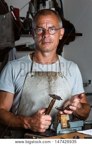 Portrait of Adult Male Goldsmith holding Hammer and Thin Silver pieces at his Workshop