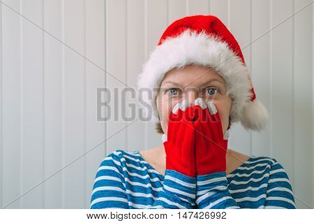 Happy woman with Christmas Santa Claus hat in cheerful holiday mood preparing for Xmas or New Year's Eve.
