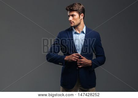 Portrait of a casual handsome man buttoning his jacket isolated on a gray background