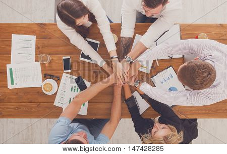 Team put hands together, show connection and alliance, top view of working table. Teambuilding in office, young businessmen and women in casual unite hands for teamwork and cooperation at new project.