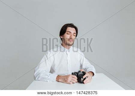Young bristled man with eyes closed sitting at the table with eyes closed isolated on the gray background