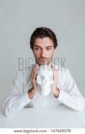 Close up portrait of a man in white shirt holding fake skull at his face isolated on the gray background
