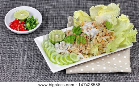 Fried rice with crab topped streamed crab,halve green lemon,sliced cucumber,lettuce and coriander served  spicy  sour filling side dish. Side view.