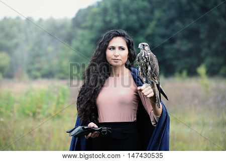 woman in a blue hooded cloak holding a falcon on his arm