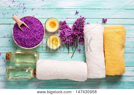 Spa concept. Sea salt in bowl bottle with aroma oil towels and candles on turquoise wooden background. Selective focus. Flat lay.