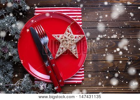 Empty late knife and fork napkin and christmas decorations in white and red colors on dark wooden table. Drawn snow effect. Christmas table setting.Top view. Place for text. Selective focus.