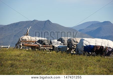 Nenets sledge loaded with household goods and the Ural Mountains on the background.