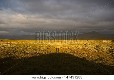 Shadow of two people standing on the hill in tundra.