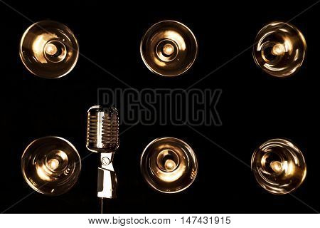 Old retro microphone on a background of black wall with incandescent