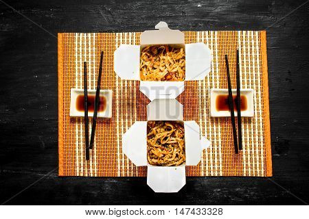 Chinese noodles with shrimp and soy sauce on bamboo tray.