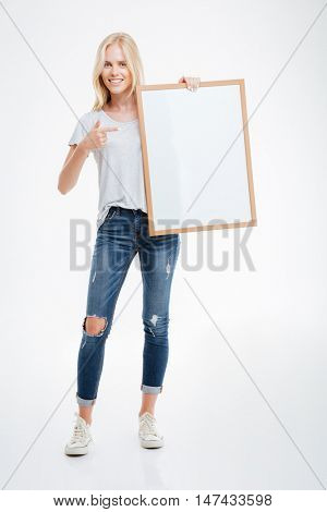 Full length portrait of a cheerful woman pointing finger at blank board isolated on a white background