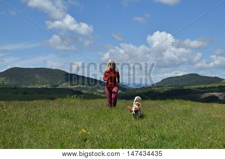 Woman And Dog Running On A Meadow