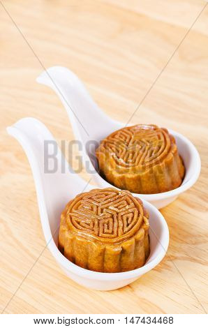 Two moon cake in white spoon on wooden background.
