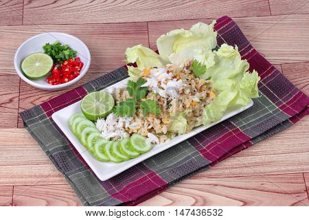 Fried rice with crab topped streamed crab,halve green lemon,sliced cucumber,lettuce and coriander  served  spicy  sour filling side dish  on wood. Side view.