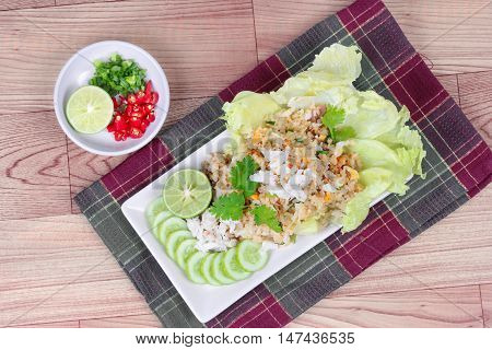 Fried rice with crab topped streamed crab,halve green lemon,sliced cucumber,lettuce and coriander  served  spicy  sour filling side dish  on wood.  Top view