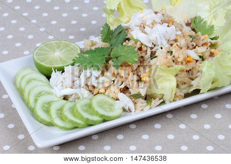 Close up of fried rice with crab topped streamed crab,halve green lemon,sliced cucumber,lettuce and coriander on gray. Selective focus.