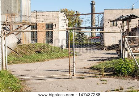 Industrial metal gate with abandoned building in background