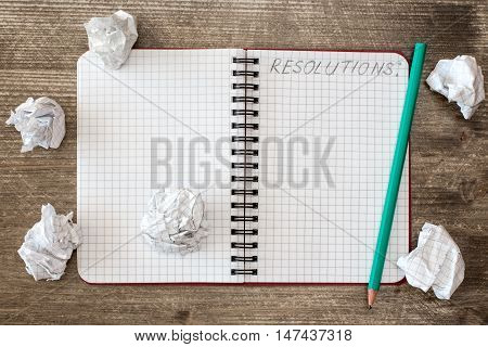 Notebook for RESOLUTIONS and crumpled paper on the wooden desk