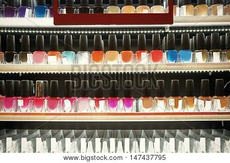 Set of different nail polish on shelf in cosmetic store