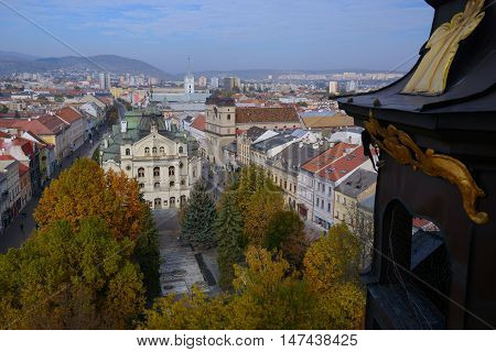 Top view of Kosice (Slovakia) from Saint Elisabeth Cathedral tower. Square with yellow trees in foreground. Town theatre in the midle of composition.