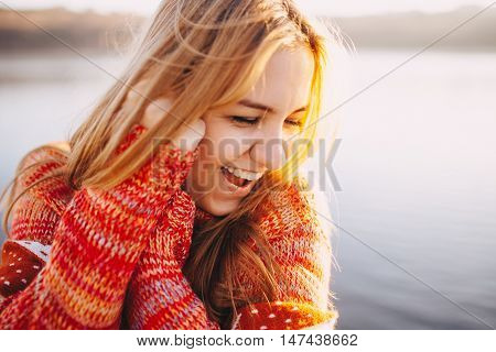 Close up hipster shy girl wearing warm clothes standing and smiling by a lake. Sun light at sunset.