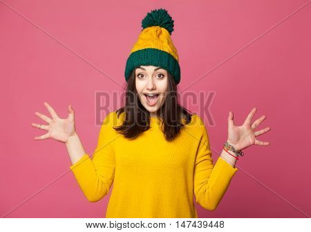 Surprised hipster girl. Excited young woman wearing a yellow winter hat and sweater throwing  hands isolated on pink background