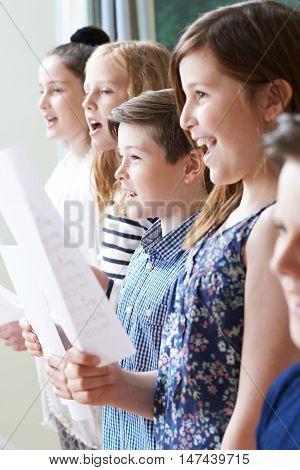 Portrait Of Group Of Children Enjoying Singing Group