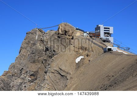 Summit station of a cable car and suspension bridge. Sex Rouge mountain peak. Travel destination in the Swiss Alps. Glacier de Diablerets ski area.