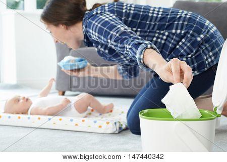 Mother Disposing Of Baby Wipe In Bin