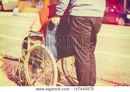 Woman in wheelchair with man pushing