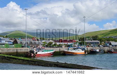 Launches in the port of Dingle, green hills