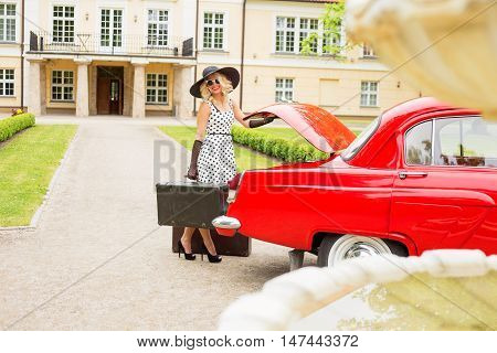 Woman dressed in coctail dress holding vintage suitecase next to red retro car
