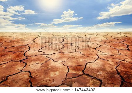 Dry cracked soil in drought land under sky background.