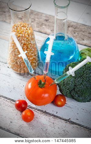 Syringe In Tomato. Genetically Modified Food Concept On Wooden Background.
